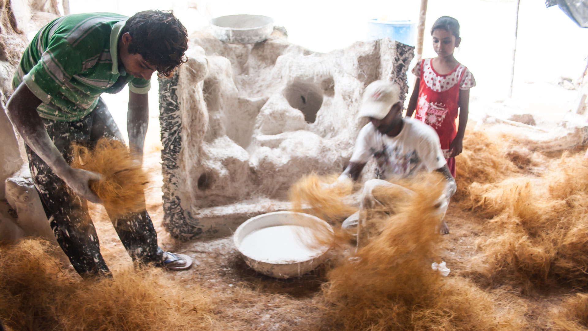 Mixing the coconut coir fibers with the plaster to build the Ganesh idol | Creating a Ganesh idol is a family trade in the Hollywood slum in Ahmedabad, India. We met some of the artists.