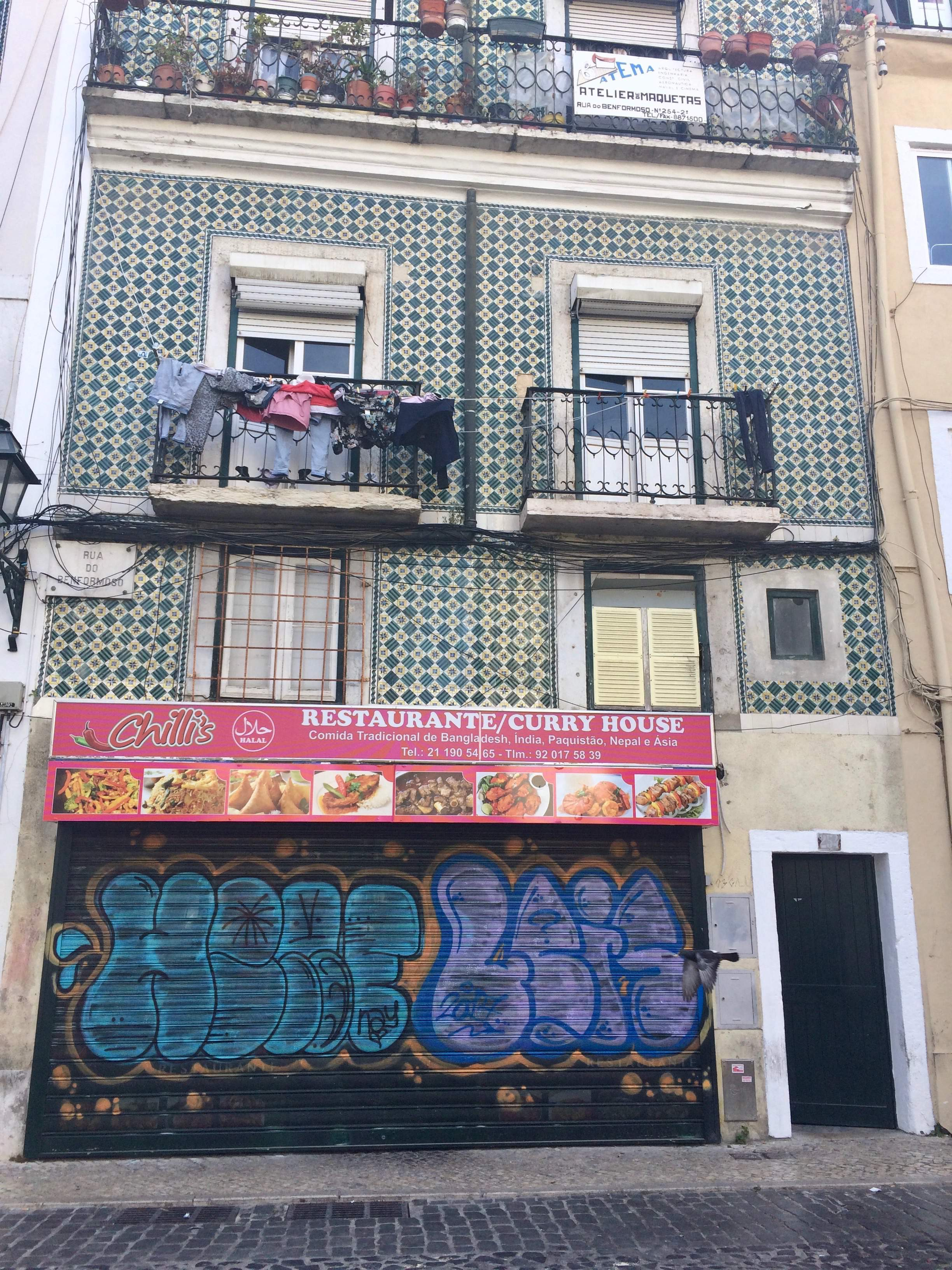 A tiled apartment building in Mouraria Lisbon with an Asian restaurant on the ground floor