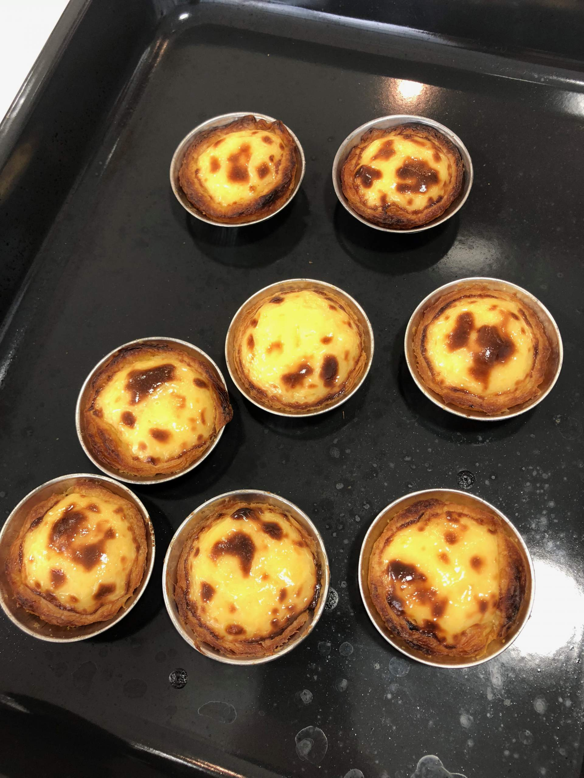 A tray of freshly baked pasteis de nata at Lisbon Cooking Academy with a special trick