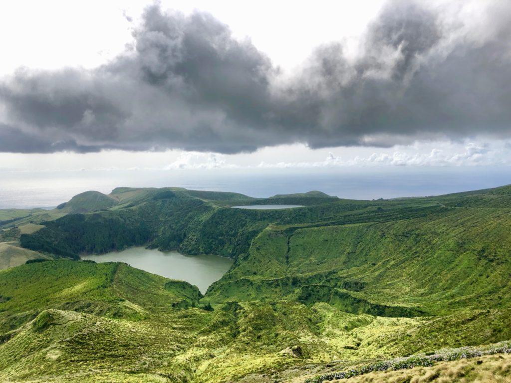 dark clouds over lagoons and green fields on Flores Island, Azores